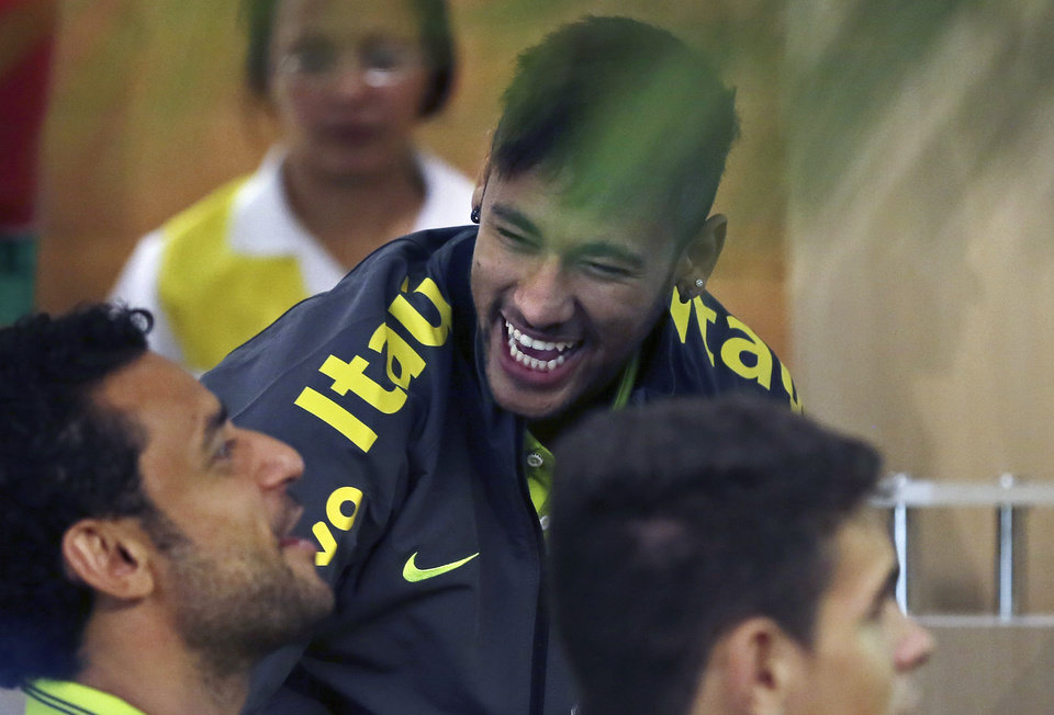 Photo - Brazil's Neymar, center, jokes around with fellow player Fred as they play a video game at the Granja Comary training center in Teresopolis, Brazil, Monday, May 26, 2014. The Brazil national team's preparations for its home World Cup got underway on Monday as the players selected by coach Luiz Felipe Scolari reported to the national soccer team. (AP Photo/Leo Correa)