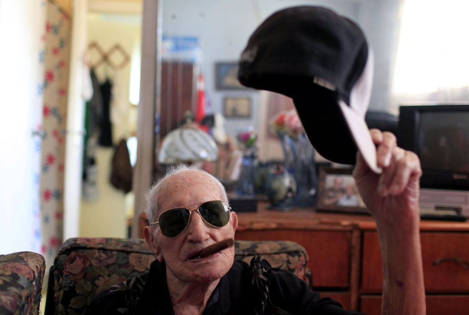 Photo - In this April 23, 2013 photo, Conrado Marrero, the world's oldest living former major league baseball player, poses for a photo as he holds his baseball cap and an unlit cigar in his mouth two days before is 102nd birthday at his home in Havana, Cuba. In addition to his longevity, the former Washington Senator has much to celebrate this year. After a long wait, he finally received a $20,000 payout from Major League baseball granted to old-timers who played between 1947 and 1979. The money had been held up since 2011 due to issues surrounding the 51-year-old U.S. embargo on Cuba, which prohibits most bank transfers to the Communist-run island. But the payout finally arrived in two parts, one at the end of last year, and the second a few months ago, according to Marrero's family. (AP Photo/Franklin Reyes)