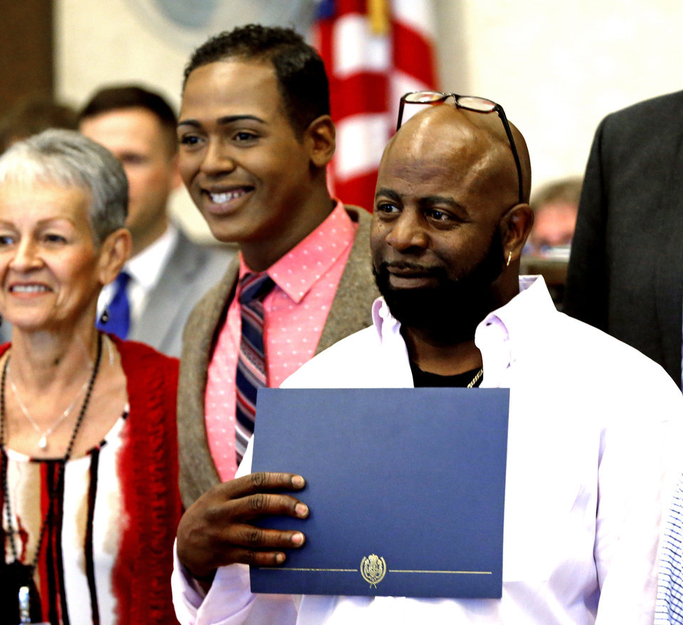Photo -  Graduates Deyon Shelly and Al Anderson pose for a picture Thursday after graduation from drug court in the Cleveland County Courthouse. [Photo by Steve Sisney, The Oklahoman]