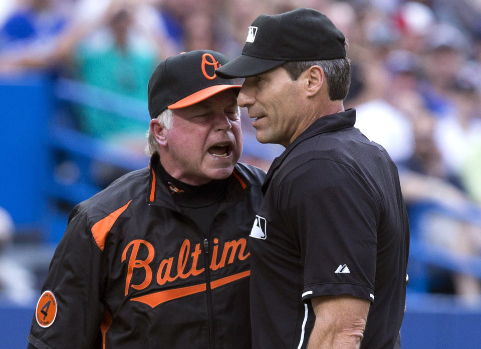 Photo - Baltimore Orioles manager Buck Showalter, left, argues a call with home plate umpire Angel Hernandez during the second inning of a baseball game against Toronto Blue Jays in Toronto on Friday, June 21, 2013. (AP Photo/The Canadian Press, Chris Young)