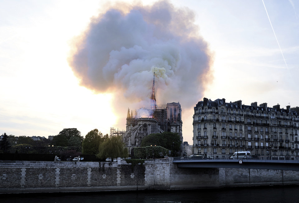 Photo - Flames and smoke rise as the spire on Notre Dame cathedral starts to collapse in Paris, Monday, April 15, 2019. Massive plumes of yellow brown smoke is filling the air above Notre Dame Cathedral and ash is falling on tourists and others around the island that marks the center of Paris. (AP Photo/Diana Ayanna)