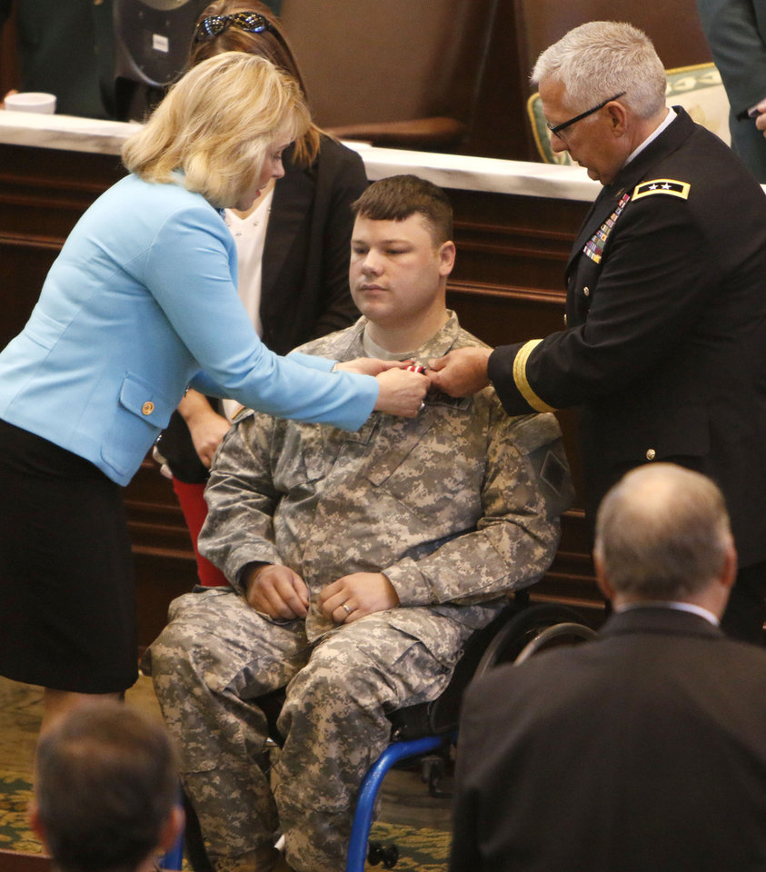 Photo -  Oklahoma Gov. Mary Fallin and Maj. Gen. Myles Deering present a medal and commendation to Sgt. E.H. Pittman during a joint session of the Oklahoma Legislature on Tuesday in Oklahoma City. Photo by Paul Hellstern, The Oklahoman   PAUL HELLSTERN -  Oklahoman