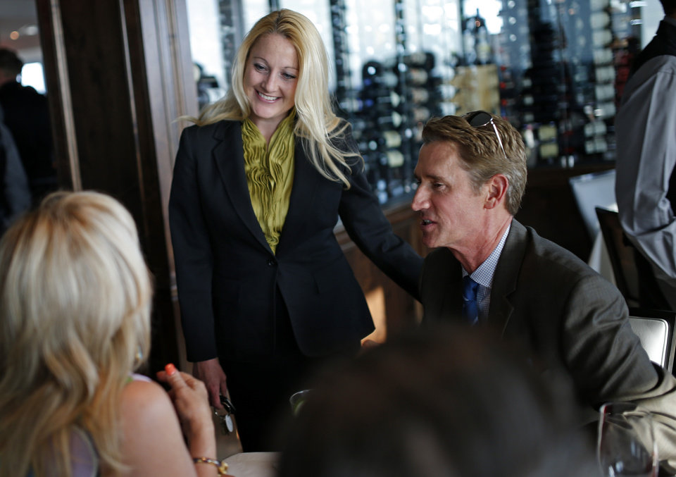 Photo - Vivian Wood with The George Prime Steakhouse talks with the crowd including Dr. Joe Phillips, at right, during a preview event inside the restaurant atop the Founders Tower in Oklahoma City, Wednesday, June, 11, 2014. Photo by Bryan Terry, The Oklahoman