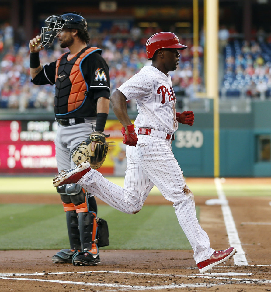Photo - Philadelphia Phillies' Jimmy Rollins, right, scores past Miami Marlins catcher Jarrod Saltalamacchia after stealing third base and then scoring on a throwing error by Saltalamacchia during the first inning of a baseball game, Tuesday, June 24, 2014, in Philadelphia. (AP Photo/Matt Slocum)