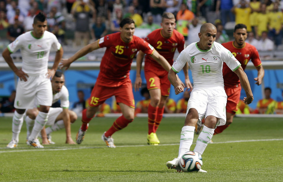 Photo - Algeria's Sofiane Feghouli scores the opening goal from the penalty spot during the group H World Cup soccer match between Belgium and Algeria at the Mineirao Stadium in Belo Horizonte, Brazil, Tuesday, June 17, 2014.   (AP Photo/Ricardo Mazalan)