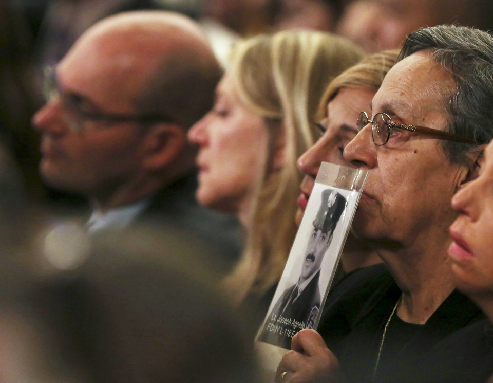 Photo - A photograph of New York Fire Department  Lt. Joseph Agnello is held during the dedication ceremony at the National September 11 Memorial Museum in New York, Thursday, May 15, 2014.  (AP Photo/The Record, Chris Pedota, Pool)