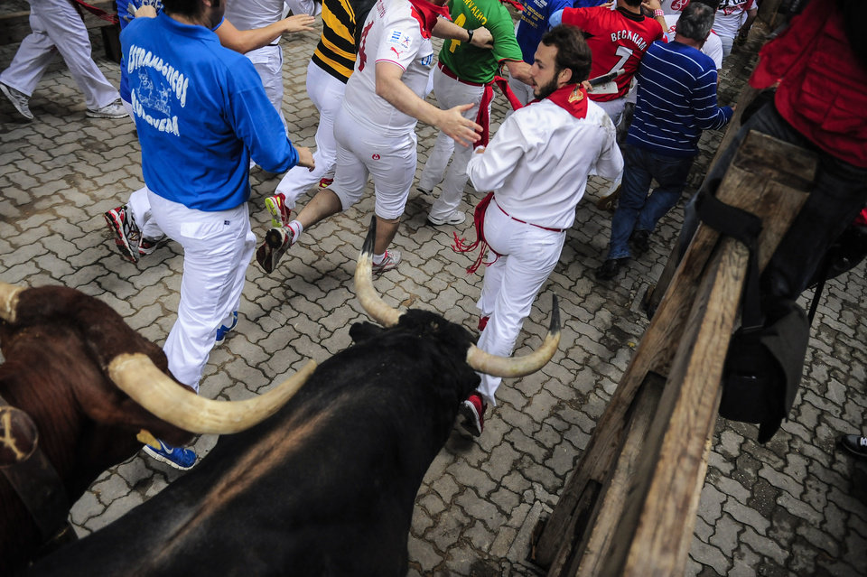 Photo - Revelers run ahead of ''Garcigrande'' fighting bulls before they come into in the bull ring, during the running of the bulls,  at the San Fermin festival, in Pamplona, Spain, Thursday, July 10, 2014. Revelers from around the world arrive to Pamplona every year to take part in some of the eight days of the running of the bulls glorified by Ernest Hemingway's 1926 novel