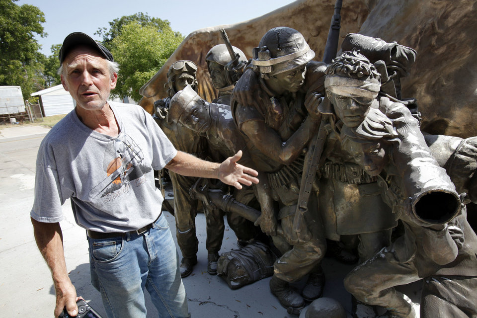 Sculptor Gareth Andrews stands next to his veterans' memorial monument Tuesday in Norman.  Photo by Steve Sisney, The Oklahoman