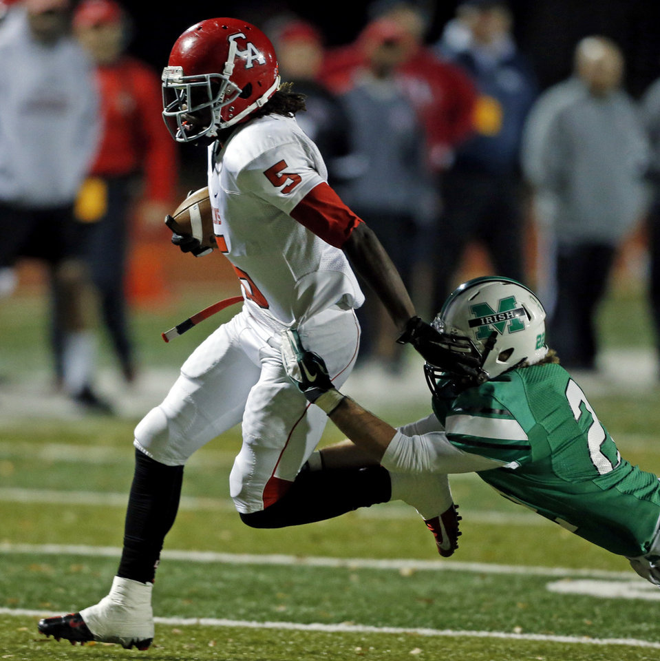 McGuinness defensive back Bradley Fritch (22) trips up Titan running back Bryan Williams (5) saving a touchdown as the Bishop McGuinness Irish play the Carl Albert Titans in a Class 5A semi-final playoff game at Harve Collins Field on Friday, Nov. 23, 2012 in Norman, Okla. Photo by Steve Sisney, The Oklahoman