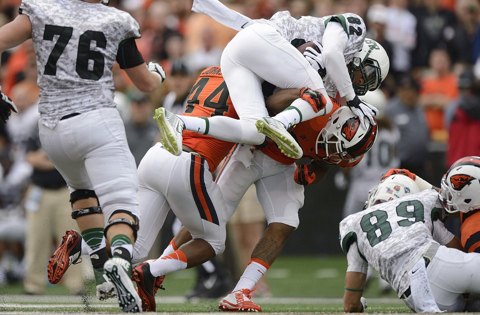 Photo - Portland State receiver Darnell Adams (82) is tackled by Oregon State safety Justin Strong during an NCAA college football game in Corvallis, Ore., Saturday, Aug. 30, 2014. (AP Photo/Troy Wayrynen)