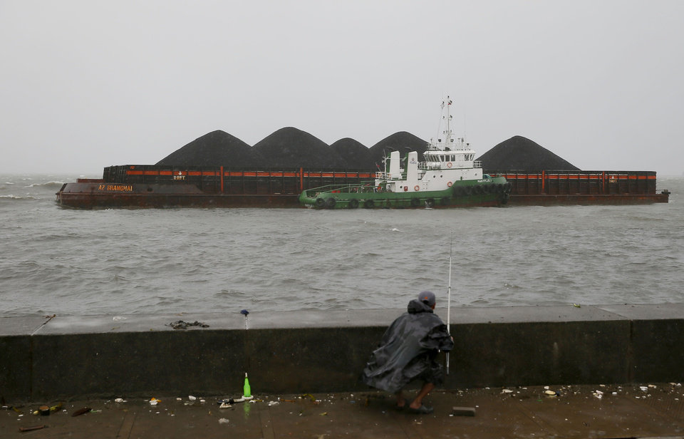 Photo - An angler prepares to fish as wayward barge AZ Shanghai carrying coal and 10 crew drifts dangerously close to a breakwater in Manila Bay due Typhoon Koppu Sunday, Oct. 18, 2015 in Manila, Philippines. The slow-moving typhoon blew ashore with fierce wind in the northeastern Philippines early Sunday, toppling trees and knocking out power and communications. Officials said there were no immediate reports of casualties. (AP Photo/Bullit Marquez)