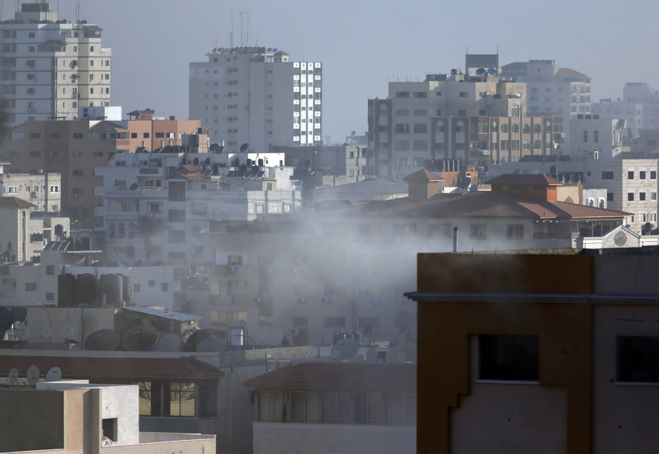 Photo - Smoke rises after a building was hit by an Israeli missile strike in Gaza City, in northern Gaza strip, Friday, July 18, 2014. The heavy thud of tank shells, often just seconds apart, echoed across the Gaza Strip early Friday as thousands of Israeli soldiers launched a ground invasion, escalating a 10-day campaign of heavy air bombardments to try to destroy Hamas' rocket-firing abilities and the tunnels militants use to infiltrate Israel. (AP Photo/Lefteris Pitarakis)