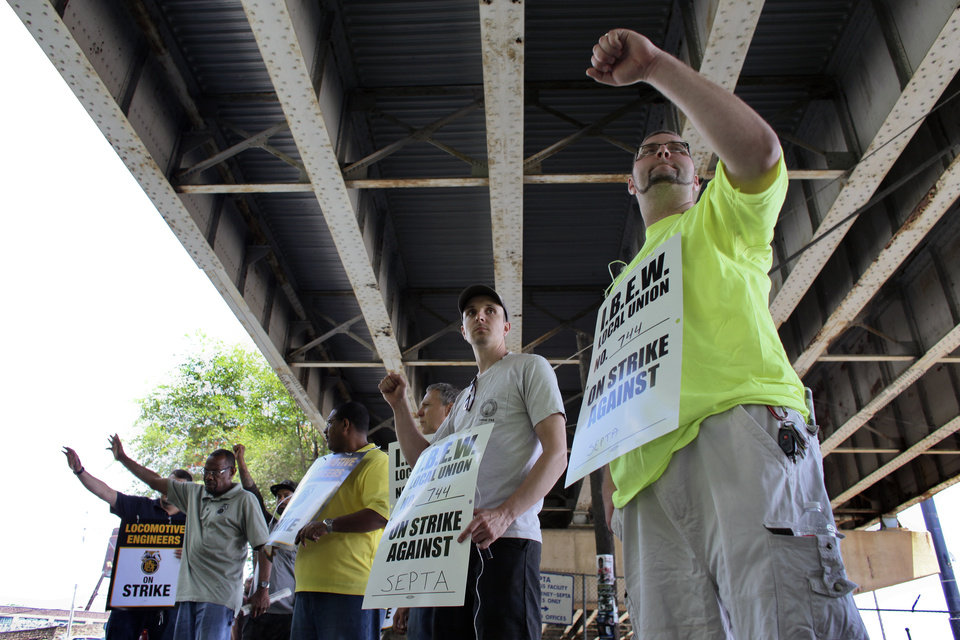 Photo - Members of the Brotherhood of Locomotive Engineers and Trainmen (BLET) union and members of the International Brotherhood of Electrical Workers (IBEW) wave to motorist while walking a picket line outside the Roberts Avenue rail yard in Philadelphia on Saturday, June 14, 2014, after the two unions went on strike at midnight Friday. Pennsylvania Gov. Tom Corbett asked President Barack Obama on Saturday to intervene the dispute between the Southeast Pennsylvania Transportation Authority and its engineers and electricians unions. (AP Photo/ Joseph Kaczmarek)