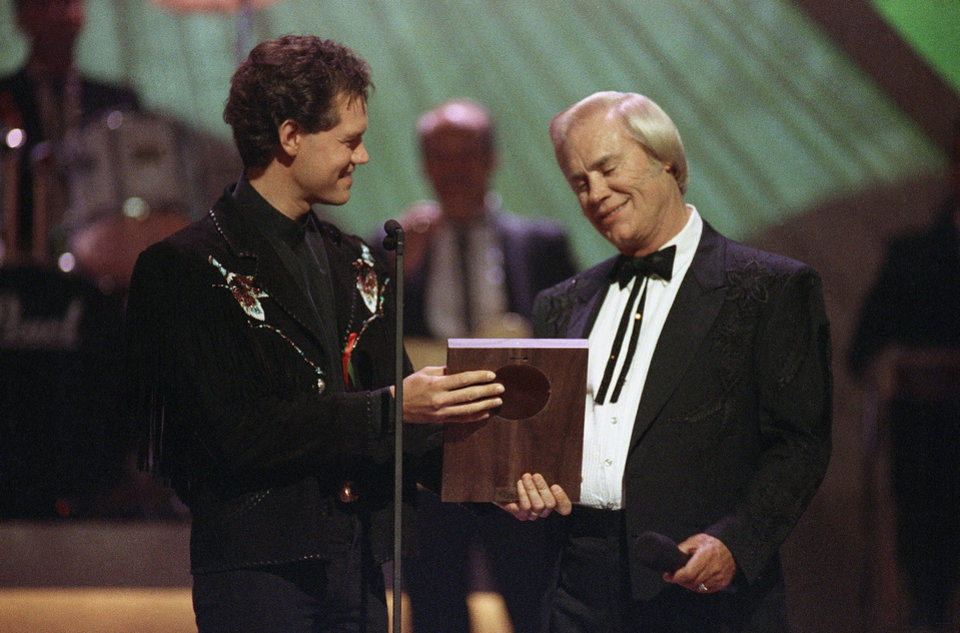 Photo - FILE - In this Sept. 30, 1992 file photo, Country music legend George Jones accepts his Country Music Hall of Fame award from Randy Travis, left, during the Country Music Association Awards show, Nashville, Tenn. Jones, the peerless, hard-living country singer who recorded dozens of hits about good times and regrets and peaked with the heartbreaking classic