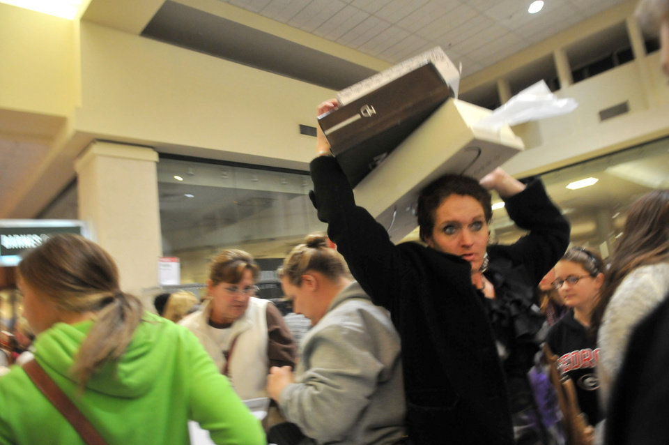 Photo -   A shopper holds boxes of boots above her head as she makes her way through a crowd during Black Friday shopping at a Belk store in Oglethorpe Mall in Savannah, Ga. on Friday, Nov. 23, 2012. (AP Photo/The Morning News, Richard Burkhart) THE EXAMINER.COM OUT; SFEXAMINER.COM OUT; WASHINGTONEXAMINER.COM OUT