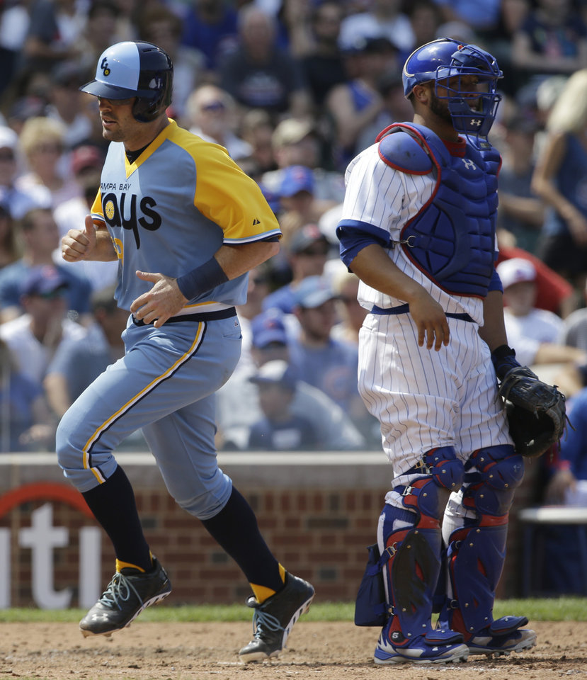 Photo - Tampa Bay Rays' Curt Casali, left, scores on a single hit by Desmond Jennings as  Chicago Cubs catcher Welington Castillo looks to the field during the fifth inning of an interleague baseball game in Chicago, Sunday, Aug. 10, 2014. (AP Photo/Nam Y. Huh)