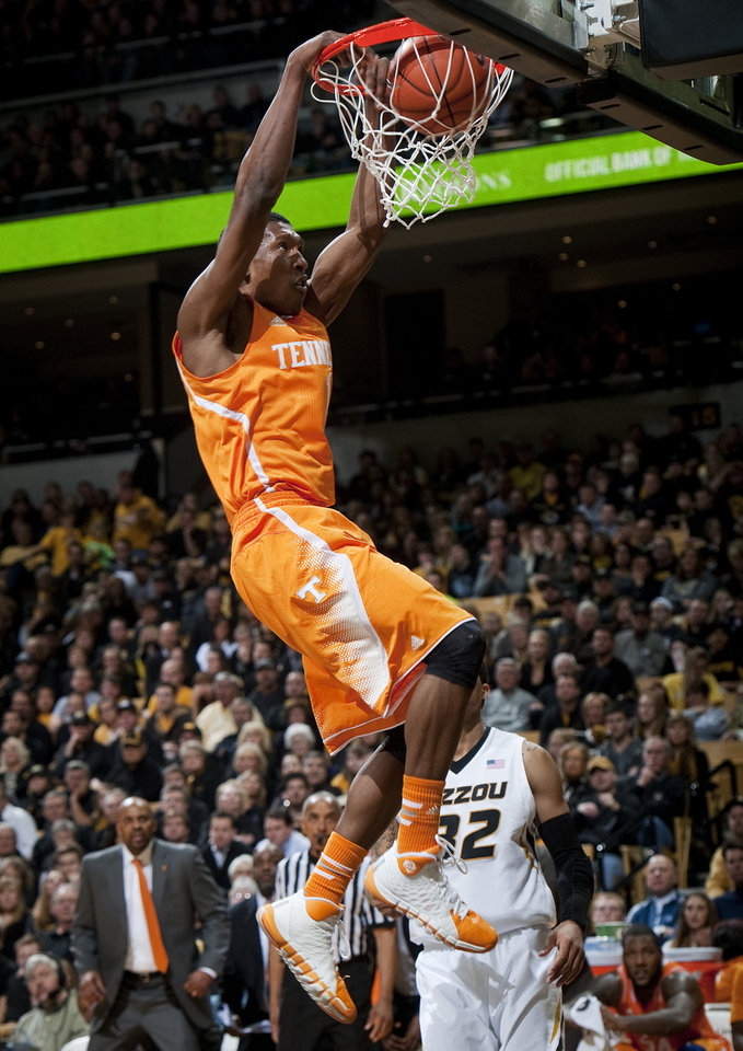 Photo - Tennessee's Josh Richardson, left, dunks the ball over Missouri's Jabari Brown during the second half of an NCAA college basketball game Saturday, Feb. 15, 2014, in Columbia, Mo. Missouri won the game 75-70. (AP Photo/L.G. Patterson)