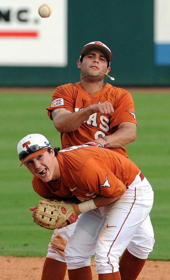 Photo - Texas' C.J. Hinojosa throws over teammate Brooks Marlow while turning a double play during the ninth inning against Texas A&M, during an NCAA college baseball tournament regional game Friday, May 30, 2014, at Reckling Park in Houston. (AP Photo/Houston Chronicle, Eric Christian Smith) MANDATORY CREDIT
