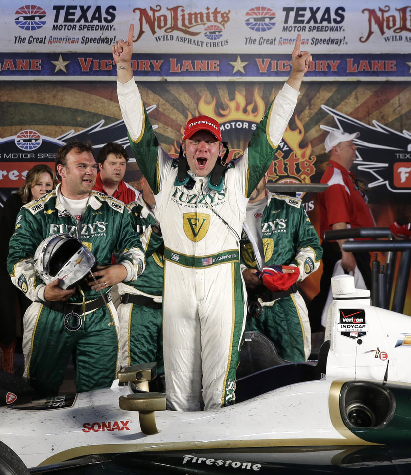 Photo - Ed Carpenter celebrates his victory in the IndyCar auto race at Texas Motor Speedway in Fort Worth, Texas, Saturday, June 7, 2014. (AP Photo/Tim Sharp)