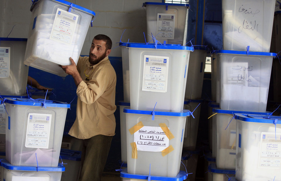 Photo - An electoral worker carries a ballot box at a counting center in Baghdad, Iraq, Sunday, April 21, 2013. Iraqis have begun counting votes from the first provincial elections since the last U.S. troops withdrew in December 2011. (AP Photo/ Karim Kadim)