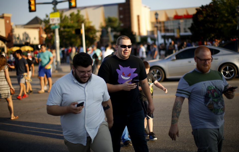 Photo - Pokemon Go players cross Reno Ave. during a meetup for players of the game in Oklahoma City at Bricktown on Friday, July 29, 2016. Photo by Bryan Terry, The Oklahoman
