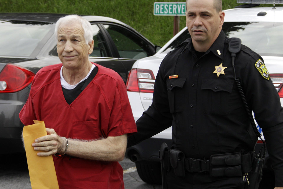 Photo -   Former Penn State University assistant football coach Jerry Sandusky, left, arrives for sentencing on child sex abuse charges at the Centre County Courthouse in Bellefonte, Pa., Tuesday, Oct. 9, 2012. Tuesday, Oct. 9, 2012. Sandusky was convicted of sexually abusing 10 boys in a scandal that rocked the university and brought down Hall of Fame coach Joe Paterno. (AP Photo/Gene J. Puskar)