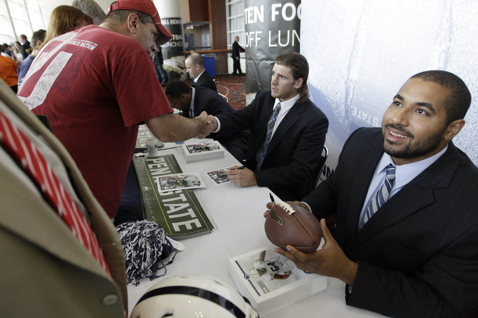 Photo -   Penn State football players Michael Mauti and John Urschel, right, sign autographs for fans as part of Big Ten Media Days and Kickoff Luncheon, Friday, July 27, 2012, in Chicago. (AP Photo/M. Spencer Green)