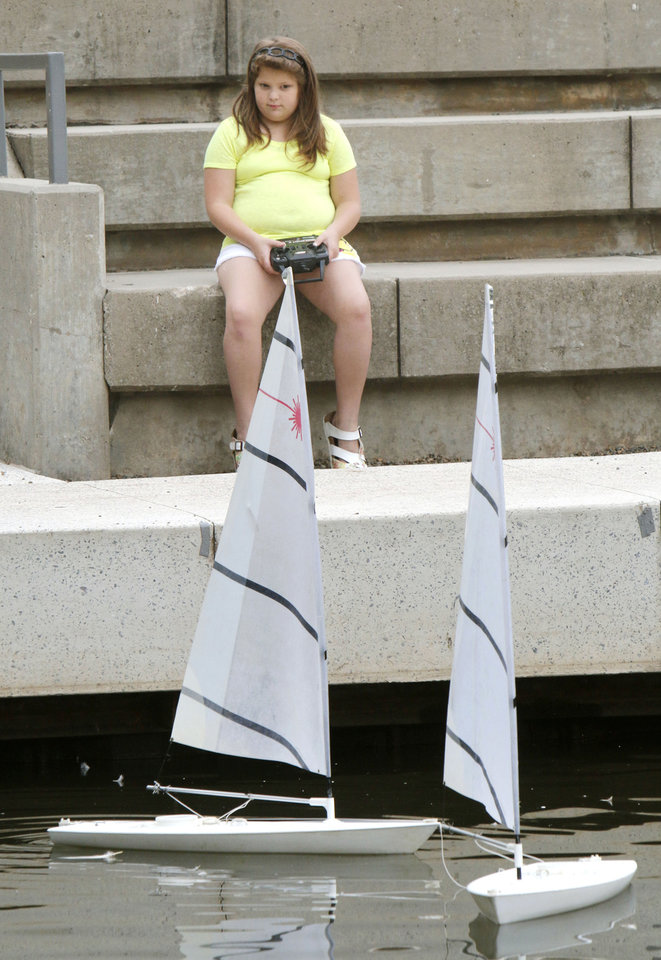 Photo -  Elizabeth Coombs, 9, operates remote control sailboats on the pond at the Myriad Gardens on Saturday. Photo by Paul Hellstern, The Oklahoman   PAUL HELLSTERN -