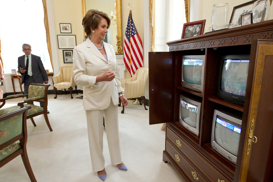 Photo -   FILE - In this June 28, 2012 file photo, House Minority Leader Nancy Pelosi of Calif., smiles as she watches the breaking news from the Supreme Court which upheld the Affordable Care Act, on Capitol Hill in Washington. It looks like a tax, smells like a tax, and the Supreme Court says it must be a tax. But politicians in both parties are squirming over how to define the Thing in President Barack Obama's health care law that requires people to pay up if they don't get health insurance. The problem for Obama is that, if the Thing is indeed a tax, he is by definition a raiser of taxes on the middle class, which he promised not to be. If that sounds like an opportunity for Republican presidential rival Mitt Romney, well, it's not that simple. (AP Photo/J. Scott Applewhite, File)
