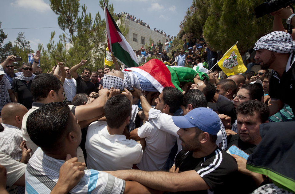 Photo - Palestinians carry the body of Mahmoud Shawamreh, 21, during his funeral in the West Bank village of Al-Ram, Tuesday, July 22, 2014. Shawamreh died after he was shot during clashes with Israeli troops Monday. (AP Photo/Majdi Mohammed)