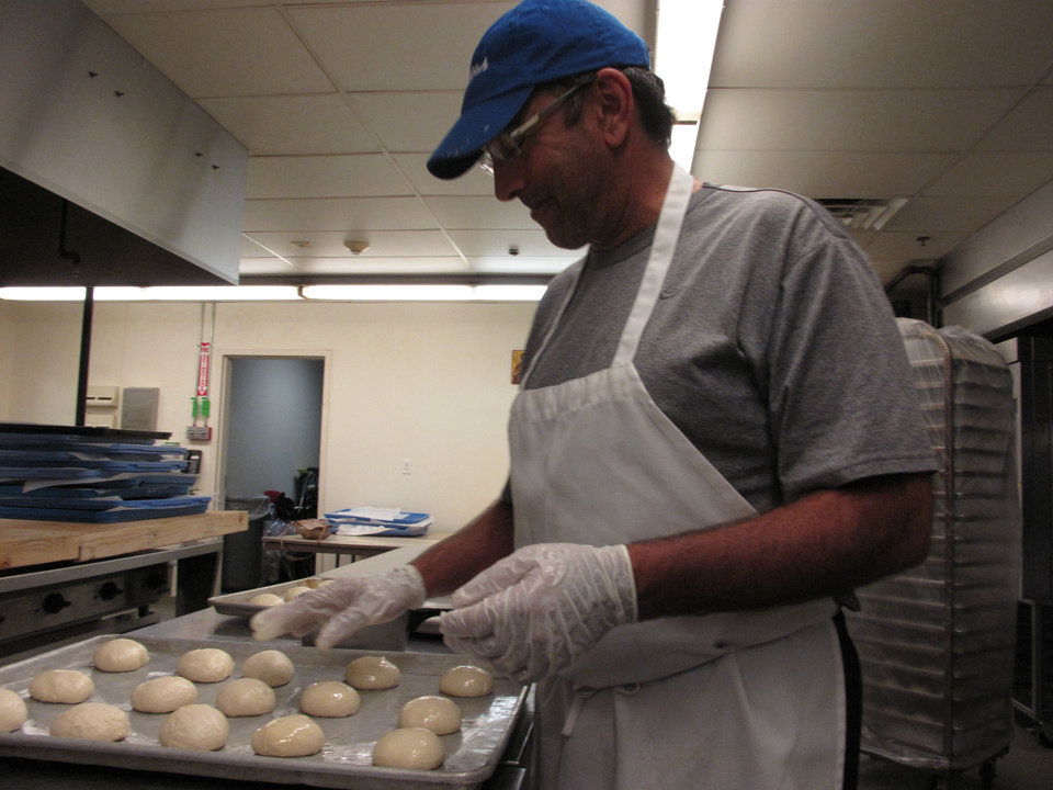 Photo - Volunteer Mike Sleem places dough on a baking sheet in the kitchen at St. Elijah Antiochian Orthodox Christian Church, 15000 N May. Photo by Carla Hinton, The Oklahoman