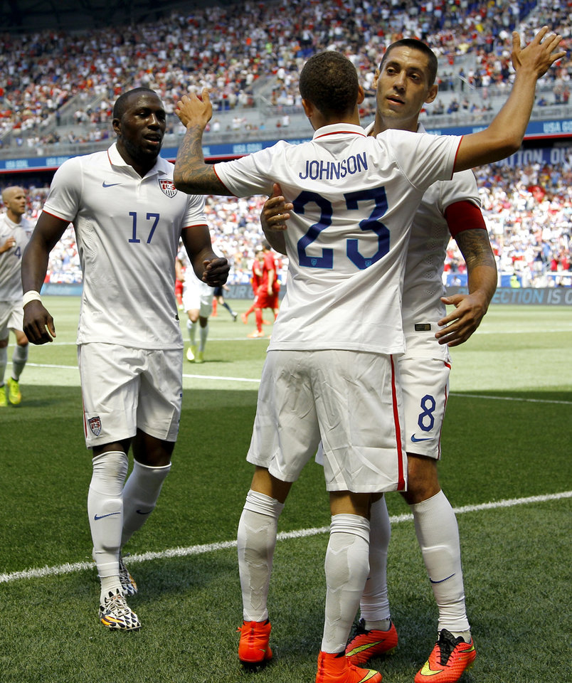 Photo - United States' Fabian Johnson (23) is congratulated by Clint Dempsey, right, and and Jozy Altidore (17) after scoring a goal on Turkey in the first half of an international soccer friendly, Sunday, June 1, 2014, in Harrison, N.J. The U.S. won 2-1. (AP Photo/Julio Cortez)