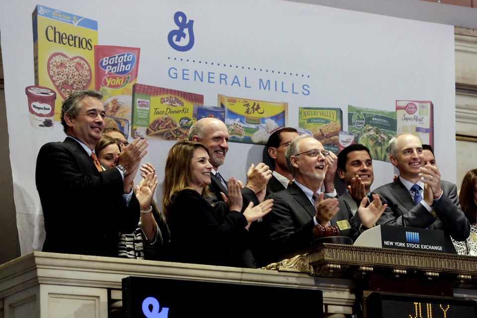 Photo - FILE - In this July 8, 2014 file photo, General Mills Chairman & CEO Kendall Powell, second from right, joins in applause as he rings the New York Stock Exchange Tuesday opening bell, July 8, 2014. The Minneapolis-based company, which last month announced a cost-cutting plan that will include a review of its manufacturing plants, is working to adapt its offerings as it grapples with the changing eating habits of Americans. (AP Photo/Richard Drew, File)