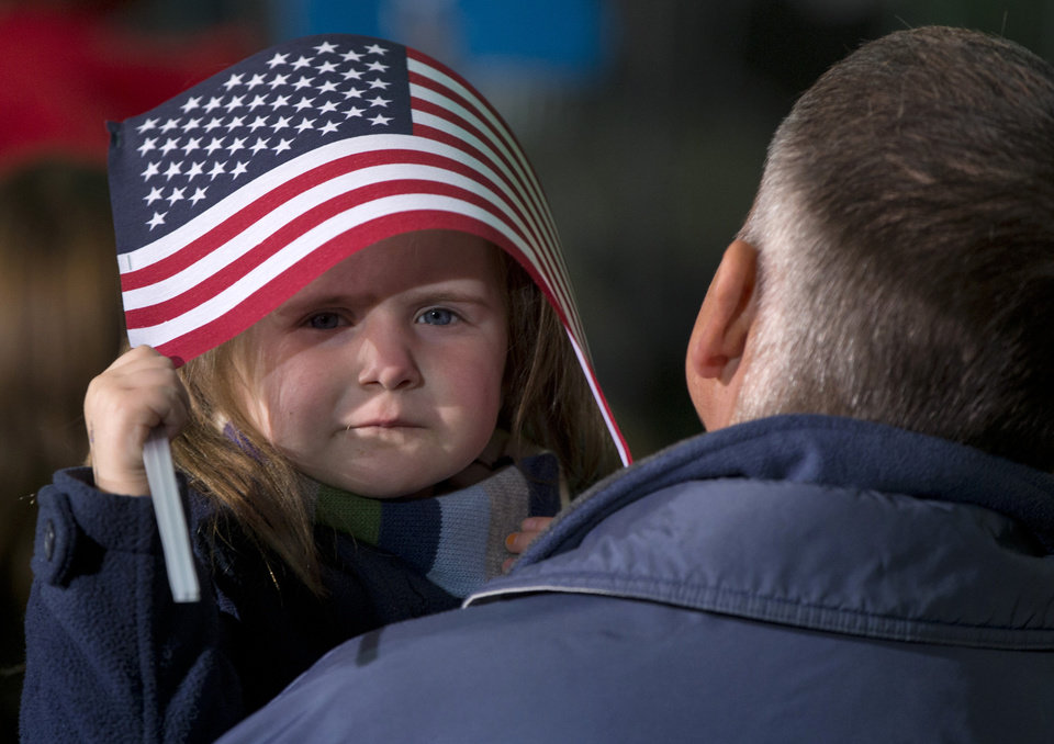 Photo -   A little girl takes shelter under and American Flag before President Barack Obama arrives to speak at a campaign event at the Franklin County Fairgrounds, Friday, Nov. 2, 2012, in Hilliard, Ohio, before heading to another campaign stop in in Springfield, Ohio. (AP Photo/Carolyn Kaster)