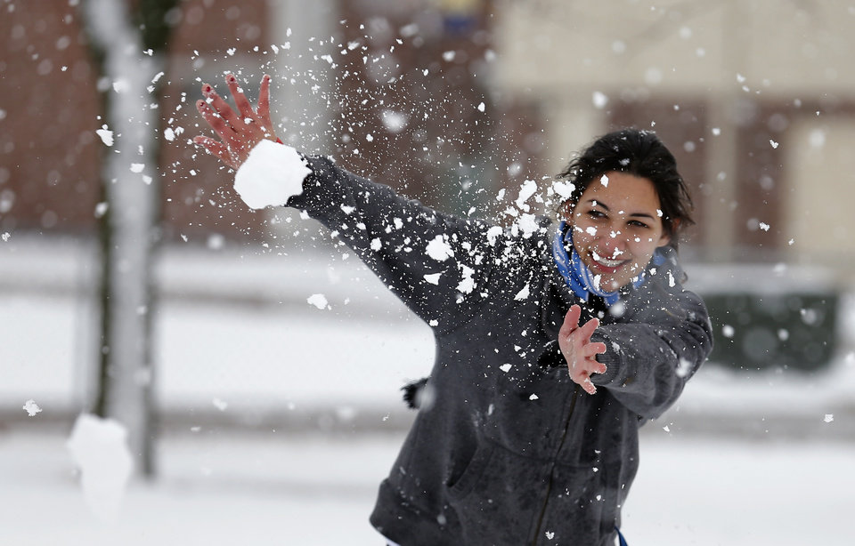 Photo - Adriana Ruiz throws a snowball at the University of Central Oklahoma in Edmond, Okla., Wednesday, Feb. 13, 2013.Photo by Sarah Phipps, The Oklahoman