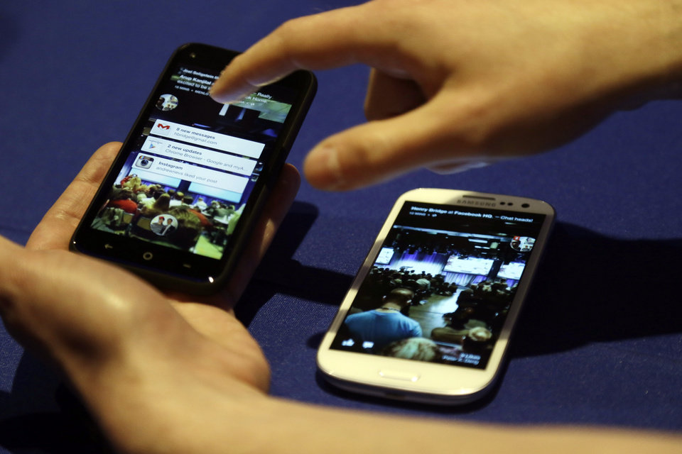 Cell phones with the a new Facebook interface are displayed at the company\'s headquarters in Menlo Park, Calif., Thursday, April 4, 2013. (AP Photo/Marcio Jose Sanchez)