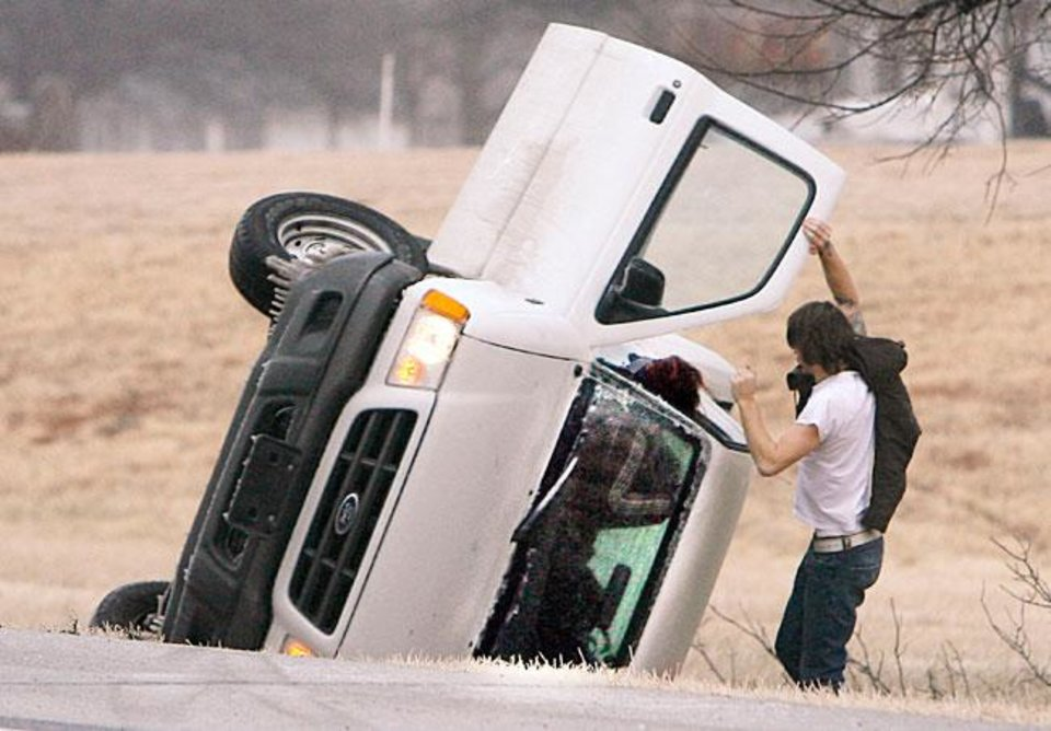 Two motorists try to escape their car which overturned on the icy Turner Turnpike near the Wellston exit outside of Wellston, Okla., Monday, Jan. 26, 2009. BY PAUL HELLSTERN, THE OKLAHOMAN