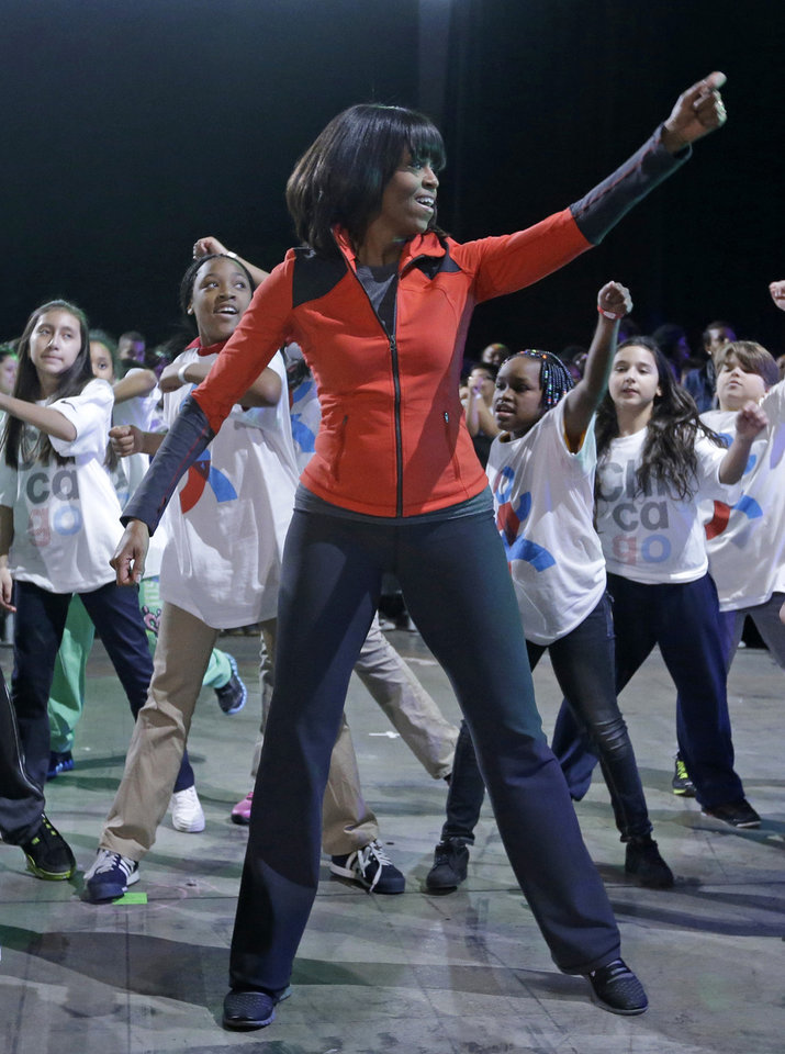 First lady Michelle Obama exercises with children from Chicago Public Schools, in her hometown of Chicago, Thursday, Feb. 28, 2013, as she makes a major announcement helping to bring back physical activity to area schools, while celebrating the third anniversary of her \'Lets Move\' program. (AP Photo/M. Spencer Green)