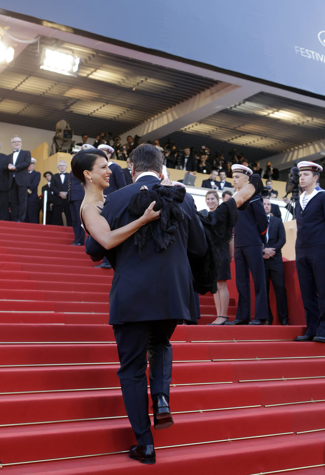 Photo - Actor Alec Baldwin carries Hilaria Thomas up the stairs for the opening ceremony and screening of Moonrise Kingdom at the 65th international film festival, in Cannes, southern France, Wednesday, May 16, 2012. (AP Photo/Lionel Cironneau) ORG XMIT: CAN184