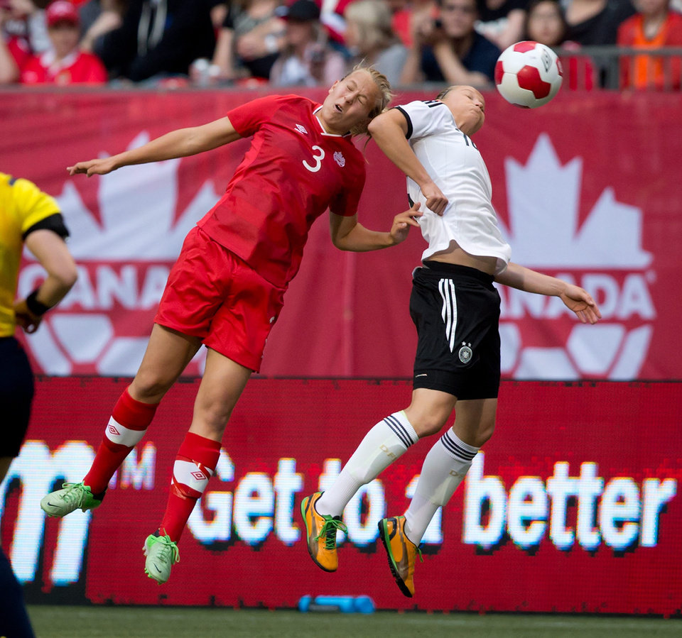 Photo - Canada's Rebecca Quinn, left, and Germany's Alexandra Popp vie for the ball during the first half of an international women's soccer game in Vancouver, B.C., on Wednesday June 18, 2014. THE CANADIAN PRESS/Darryl Dyck