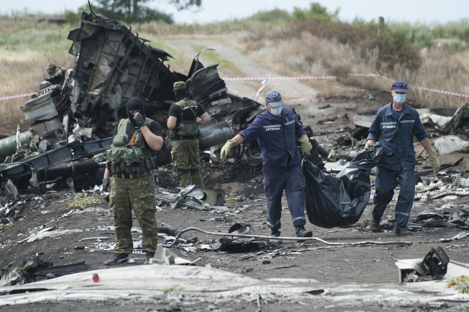 Photo - Ukrainian Emergency workers carry a stretcher with a victim's body in a bag as pro-Russian fighters stand in guard at the crash site of Malaysia Airlines Flight 17 near the village of Hrabove, eastern Ukraine, Sunday, July 20, 2014. Rebels in eastern Ukraine took control Sunday of the bodies recovered from downed Malaysia Airlines Flight 17, and the U.S. and European leaders demanded that Russian President Vladimir Putin make sure rebels give international investigators full access to the crash site. (AP Photo/Evgeniy Maloletka)