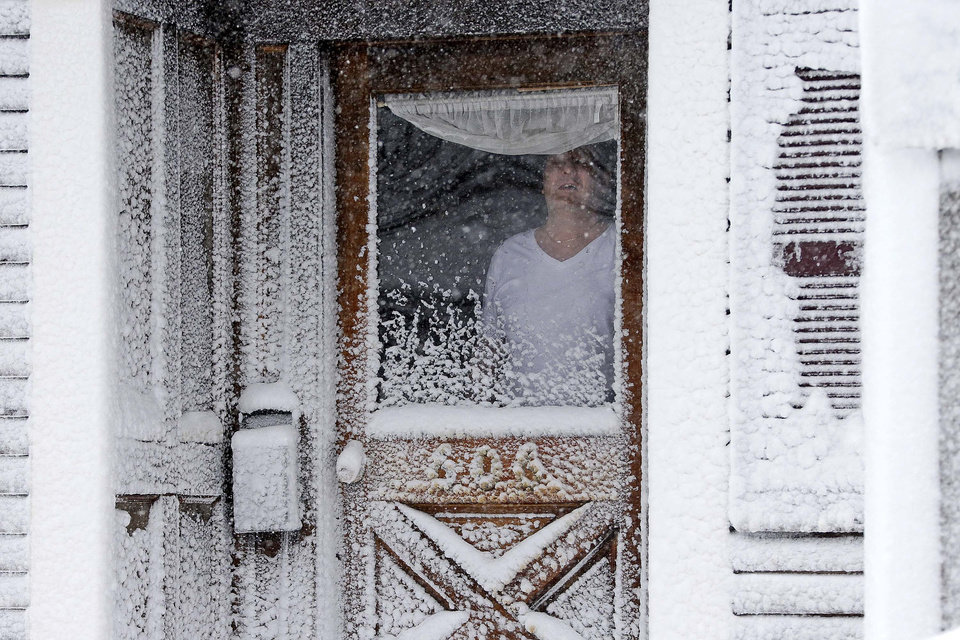 A resident of Third Street in the South Boston neighborhood of Boston looks out of his snow-coated front door Saturday, Feb. 9, 2013. A behemoth storm packing hurricane-force wind gusts and blizzard conditions swept through the Northeast overnight. (AP Photo/Gene J. Puskar)