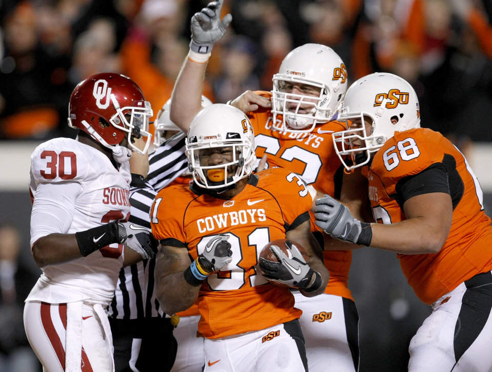 Photo - Oklahoma State's Jeremy Smith (31), Oklahoma State's Jordan Taormina (63), and Oklahoma State's Lane Taylor (68) celebrate in front of Oklahoma's Javon Harris (30) after a touchdown during the Bedlam college football game between the University of Oklahoma Sooners (OU) and the Oklahoma State University Cowboys (OSU) at Boone Pickens Stadium in Stillwater, Okla., Saturday, Nov. 27, 2010. Photo by Bryan Terry, The Oklahoman