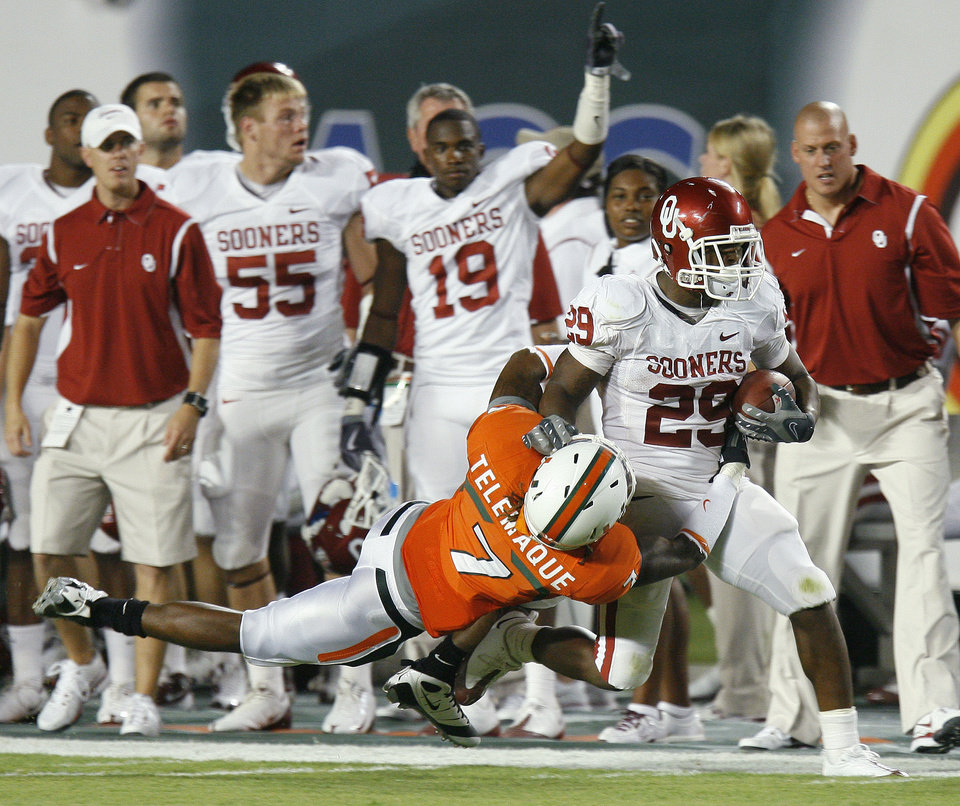 Photo - OU's Chris Brown fights off Miami's Vaughn Telemaque during the college football game between the University of Oklahoma (OU) Sooners and the University of Miami (UM) Hurricanes at Land Shark Stadium in Miami Gardens, Florida, Saturday, October 3, 2009. Photo by Bryan Terry, The Oklahoman ORG XMIT: KOD