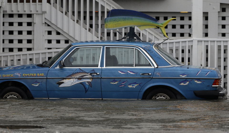 Photo - A vehicle sits in rising waters as Hurricane Arthur passes through the area in Nags Head, N.C., Friday, July 4, 2014. (AP Photo/Gerry Broome)