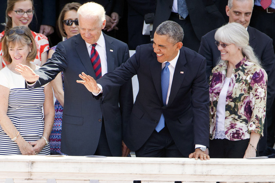 Photo - Vice President Joe Biden, left, and President Barack Obama wave to members of the Tragedy Assistance Program for Survivors (TAPS), for people who have a family members who died in the military, after Obama spoke during a Memorial Day Observance at Arlington National Cemetery in Arlington, Va., Monday, May 26, 2014. (AP Photo/Jacquelyn Martin)