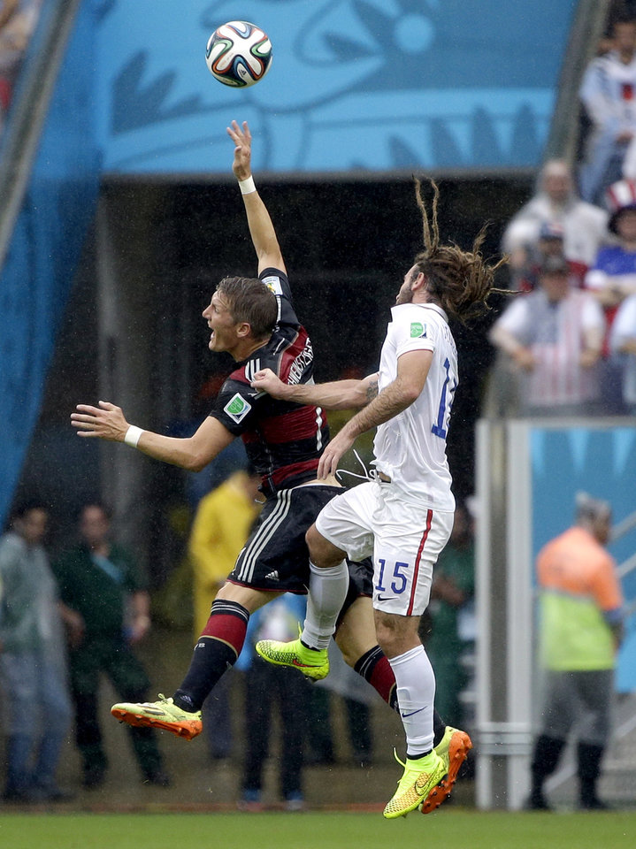 Photo - CORRECTS ID TO KYLE BECKERMAN, NOT JERMAINE JONES - United States' Kyle Beckerman goes up against Germany's Bastian Schweinsteiger during the group G World Cup soccer match between the USA and Germany at the Arena Pernambuco in Recife, Brazil, Thursday, June 26, 2014. (AP Photo/Ricardo Mazalan)