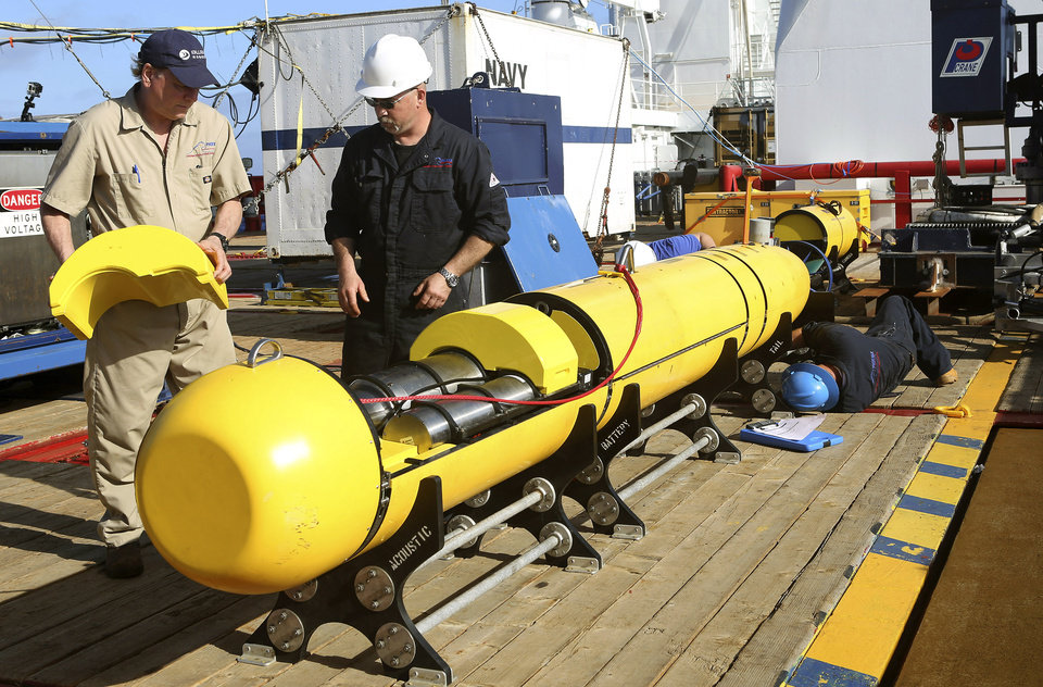 Photo - In this Monday, April 14, 2014, photo provided by the Australian Defense Force Phoenix International's Chris Minor, right, and Curt Newport inspect an autonomous underwater vehicle before it is deployed from ADV Ocean Shield in the search of the missing Malaysia Airlines Flight 370 in the southern Indian Ocean. The search area for the missing Malaysian jet has proved too deep for the robotic submarine which was hauled back to the surface of the Indian Ocean less than half way through its first seabed hunt for wreckage and the all-important black boxes, authorities said on Tuesday. (AP Photo/Australian Defense Force, Lt. Kelli Lunt) EDITORIAL USE ONLY