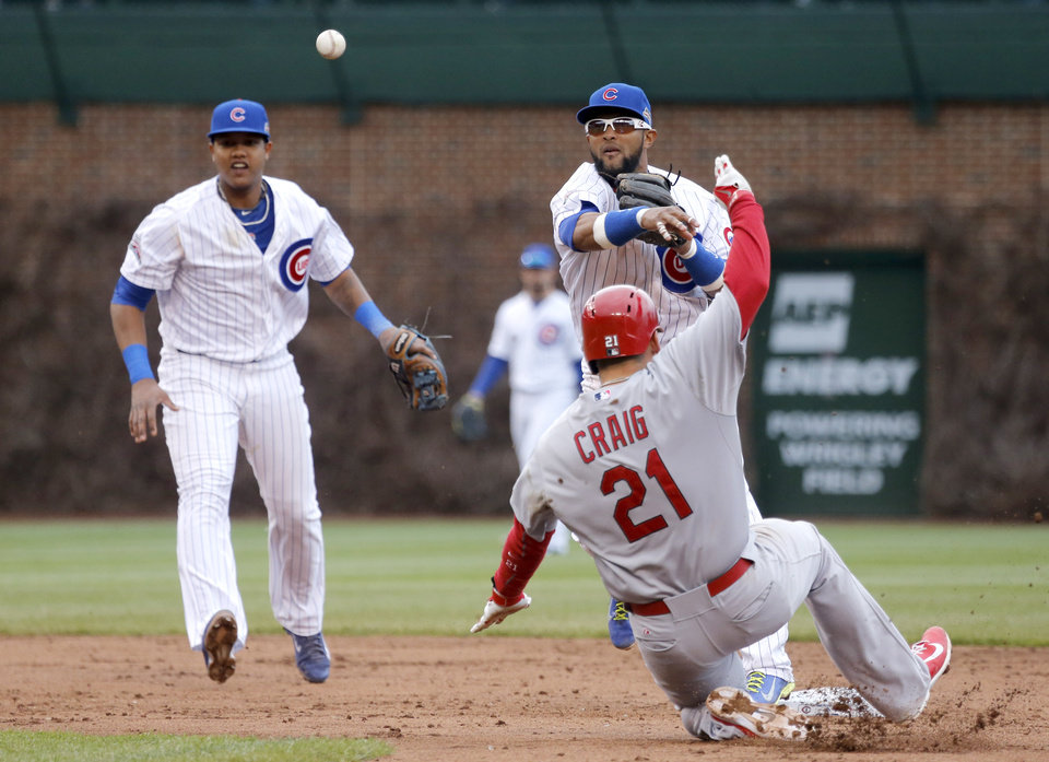 Photo - Chicago Cubs second baseman Emilio Bonifacio relays to first after forcing out St. Louis Cardinals' Allen Craig (21) at second during the sixth inning of a baseball game Friday, May 2, 2014, in Chicago. The Cardinals Jon Jay was out at first for the double play. Watching the action is shortstop Starlin Castro. (AP Photo/Charles Rex Arbogast)