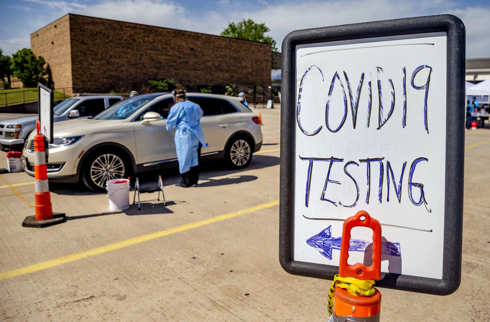 Photo - Canadian County Health Department employees collect samples from a drivers during the Canadian County Health Department's Covid-19 drive thru Testing Event at Yukon Middle School on Wednesday, May 6, 2020, in Yukon, Okla. [Chris Landsberger/The Oklahoman]